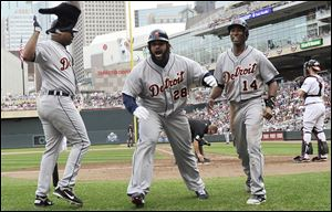 Detroit Tigers slugger Prince Fielder, center, celebrates with Delmon Young, left, and Austin Jackson after Fielder's two-run home run off Minnesota Twins pitcher Jared Burton in the eighth inning Sunday in Minneapolis. The Tigers won 2-1.
