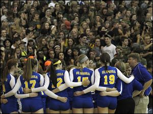 With their fans dressed for battle in the background, St. Ursula head coach John Buck huddles with his team.