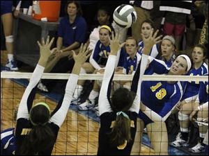 Notre Dame defenders jump to block kill by St. Ursula's Maddie Burnham.