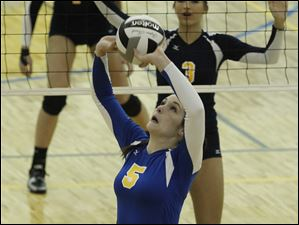 St. Ursula's Katie McKernan sets during a game at SUA in Toledo. NDA players from left are Payton Bowyer and Morgan Fioritto.
