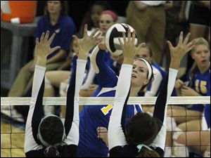St. Ursula's Maddie Burnham spikes the ball through the hands of Notre Dame's Morgan Loucks, #9, and Maddy Smith.