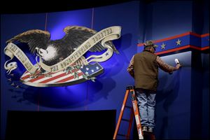 A worker cleans lint from the backdrop of the stage ahead of the first presidential debate. President Obama and GOP challenger Mitt Romney will go head to head for the first time today at the University of Denver. PBS veteran Jim Lehrer will moderate the debate, which is expected to focus on the economy.