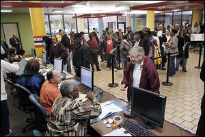 Voters wait to be checked in at the Lucas County early voting site at Summit Plaza in Toledo last fall.