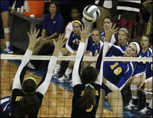 Notre Dame defenders jump to block a kill by St. Ursula's Maddie Burnham.