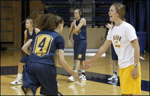UT senior and team captain Naama Shafir, left, slaps hands with graduate assistant/manager Jessica Slagle during practice Tuesday at UT's Savage Arena.