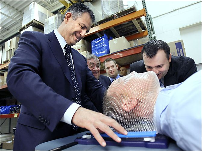 Francisco Sanchez, U.S. undersecetary of commerce for international trade, tests an embrace thermal plastic mask on Andrew Milanoski during Mr. Sanchez's visit to Toledo.