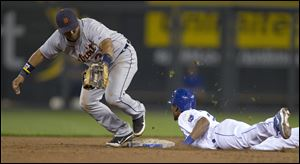 Kansas City Royals' Jarrod Dyson (1) dives back to the base during an attempted pick-off by Detroit Tigers second baseman Ramon Santiago (39) during the fifth inning.