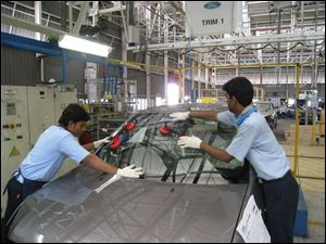 Employees work on a car at the Ford India plant in Chennai, India. Ford has invested $875 million in India since its 1995 arrival.