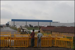 Security stands guard outside the Tata Nano production plant in Singur, India. Violent protests caused Tata Motors to abandon its nearly completed plant in Singur, depriving the rural farming communities of West Bengal of thousands of new jobs.