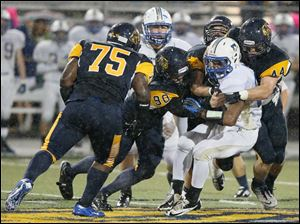 Whitmer players Joenathan Mays (75), Jacob LaPoint (90), Devin Thomas (1), and Jack Linch (44), tackle Findlay player Vance Settlemire (23).