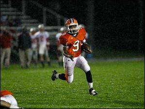 Sylvania Southview's Keith Gilmore runs the ball downfield through the rain.
