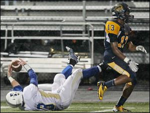 Findlay's Jimmy Orwick (13) bobbles the ball but makes the catch as Whitmer's Mike Moore (13) defends during the second.