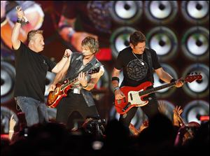 Rascal Flatts members left to right Gary LeVox,  JoeDon Rooney, and Jay DeMarcus perform Thursday at the Huntington Center.