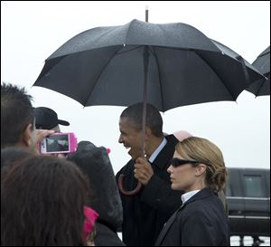 President Barack Obama greets people on the tarmac as he arrives on Air Force One in the rain at Cleveland Hopkins International Airport on Friday in Cleveland.