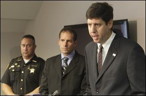 From left, Ottawa County Sheriff Steve Levorchick, and Kevin Graber from the DEA, listen as U.S. attorney Steven M. Dettlebach discusses the indictments.