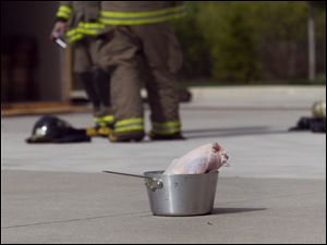 Firefighters prepare to drop a frozen turkey into a pot of boiling frying oil Saturday.