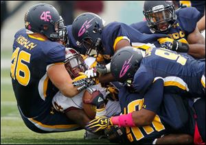 Central Michigan running back Anthony Garland is tackled by Toledo defenders, including  Hank Keighley, left, Robert Bell, bottom and Allen Covington, front right, Saturday at the Glass Bowl.