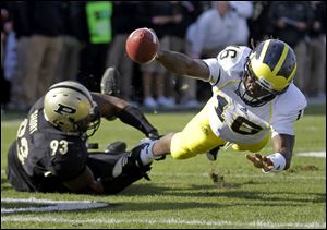 Michigan quarterback Denard Robinson, right, dives to the one-yard line as he's tackled by Purdue defensive tackle Kawann Short on Saturday in West Lafayette, Ind.