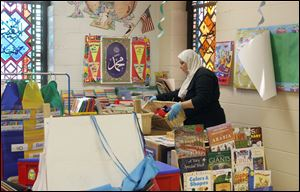Kindergarten teacher Manal El-Sheikh looks for items that she can save from her classroom at the center.