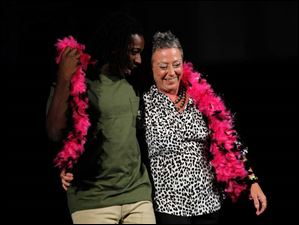 Seth Hillard escorts breast cancer survivor Lisa Hager down the runway.