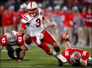 Nebraska quarterback Taylor Martinez (3) is tripped up by Ohio State's Storm Klein (32).