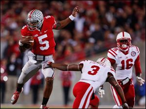 Buckeyes' quarterback Braxton Miller (5) scrambles against  Nebraska defenders during the second quarter.