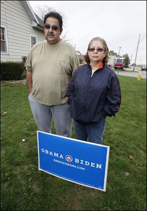Joe and Diana Rocha display a campaign sign for President Obama outside their Archbold home. The Rochas said one night this week a young man in a pickup stopped at their home shortly after midnight, took their Obama campaign signs, and replaced them with Romney campaign signs. They notified Archbold police and then replaced the Romney signs with new Obama signs.