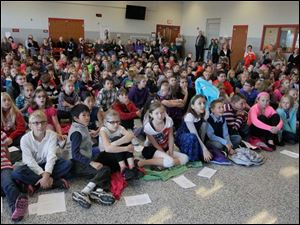 Fourth graders watch on the screen as the contents of the time capsule are revealed.