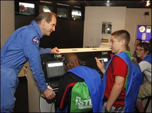 Flight director Reed Steele talks to Springfield 8th grader Nathan Thomas, standing, in the space station as part of the Fall STEM Challenge. The Educational Service Center (ESC) of Lake Erie West , sponsor of the Challenger Learning Center of Lake Erie West in Oregon, Ohio, is hosting the challenge.