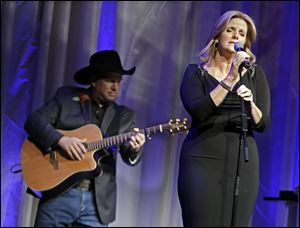 "Trisha Yearwood is accompanied by her husband, Garth Brooks, as she sings ""Wind Beneath My Wings,"" a song written by Larry Henley, as Henley is inducted into the Nashville Songwriters Hall of Fame."