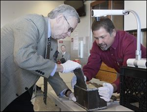 Bowling Green mayor Dick Edwards, left, and Mike Hammer, Public Works Superintendent for the city, open a time capsule.