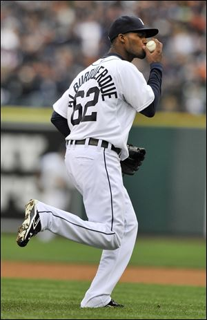 Detroit Tigers relief pitcher Al Alburquerque kisses the ball before throwing out Oakland Athletics Yoenis Cespedes at first base during the ninth inning of Game 2 of the American League division baseball series.