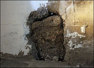 A portion of the basement wall is deteriorating because of moisture that has collected since the power has been shut off.