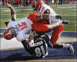 Bowling Green's Ryland Ward (15) and Aaron Foster tumble over Akron wide receiver Tyrell Goodman (81) after he caught a touchdown pass in the end zone Saturday.