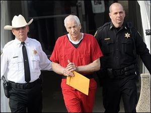 Jerry Sandusky is escorted from Centre County Courthouse after sentencing Tuesday.