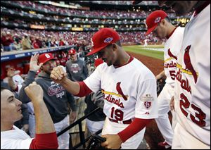 St. Louis Cardinals center fielder Jon Jay is congratulated by teammates as he returns to the dugout after catching a fly ball at the warning track to retire Washington Nationals' Danny Espinosa during the sixth inning.
