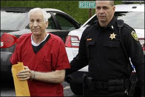 Former Penn State University assistant football coach Jerry Sandusky, left,  arrives for sentencing on child sex abuse charges at the Centre County Courthouse in Bellefonte, Pa.