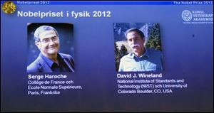 Photographs of the 2012 Nobel Prize laureates in Physics Serge Haroche from France, left, and David Wineland from the U.S. are presented on a screen during a media conference at the Royal Swedish Academy of Science in Stockholm, Sweden.