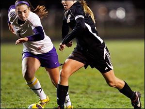 Perrysburg's Maddy Williams (12) moves the ball against  Maumee's Bailee Patterson.