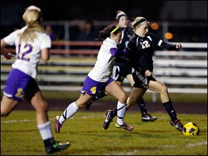 Perrysburg's Maddy Williams (12) breaks away from  Maumee's Brynn Sautter.