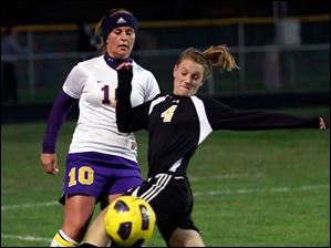 Perrysburg's Lucy Walton (4) moves the ball past  Maumee's Kara Bottles (10).