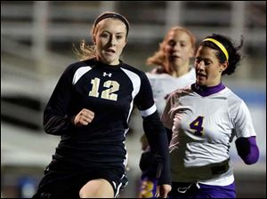 Perrysburg's Maddy Williams (12) breaks away from  Maumee's Brynn Sautter (4) en route to scoring another goal.