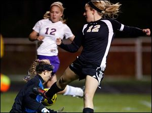 Perrysburg's Maddy Williams (12) takes a shot against  Maumee  goalie Jacq Korsog.