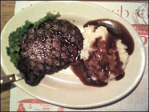 Ribeye steak with mashed potatoes and gravy.