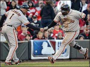 San Francisco Giants' Pablo Sandoval is congratulated by third base coach Tim Flannery after hitting a two-run home run Wednesday in