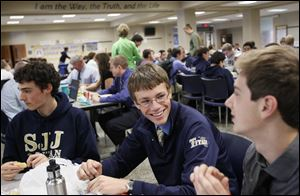 St. John's Jesuit High School senior Sean Wheelock, center, earned a perfect score on the PSAT, the SAT, and the ACT.