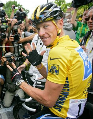 Lance Armstrong, of Austin, Texas, surrounded by press photographers, signaling seven,  for his seventh straight win in the Tour de France cycling race, prior to the start of the 21st and final stage of the race,  between Corbeil-Essonnes, south of Paris, and the French capital.