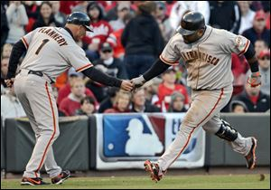 San Francisco Giants' Pablo Sandoval is congratulated by third base coach Tim Flannery after hitting a two-run home run Wednesday in Cincinnati.