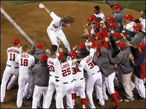 Washington Nationals' Jayson Werth leaps onto home plate after hitting a walk-off home run in the ninth inning against the St. Louis Cardinals.
