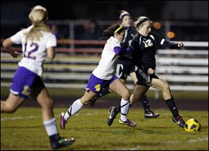 Perrysburg's Maddy Williams (12) breaks a way from  Maumee's Brynn Sautter. Williams' two goals in the game helped pace the Yellow Jackets to the NLL Championship.